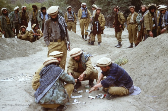 Mujahideen construct models of buildings in the valley they will attack, using match boxes, cigarette packs and slips of cardboard.