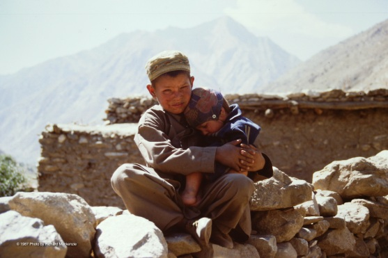 A young boy takes good care of his little brother in a Nuristan village.