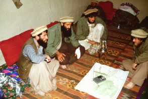 Commander Najmuddin -- with a Soviet prisoner (at right), a Stinger operator (on his left) and a key aide in his tiny guest room.